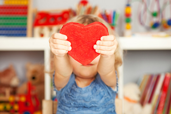 Happy child with red paper heart